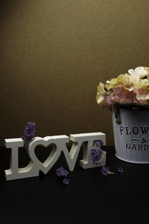 Flowers with word Love on wooden planks background, empty space for text and love concept. Stock Photo