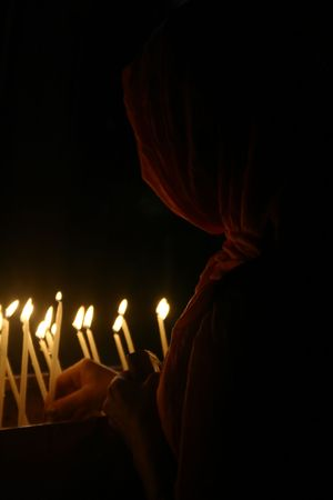 purdah: prayer with candle in church Stock Photo