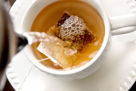 making tea; closeup of a tea cup with tea bag inside