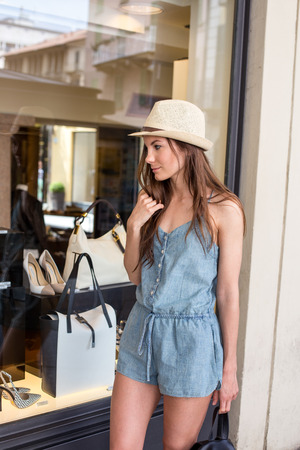 window display: attractive stylish girl looking at display window summer day Stock Photo