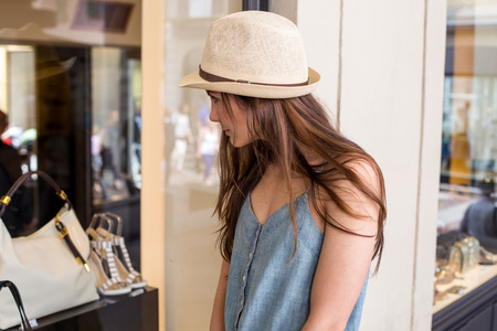 shop window display: attractive stylish girl looking at display window summer day Stock Photo
