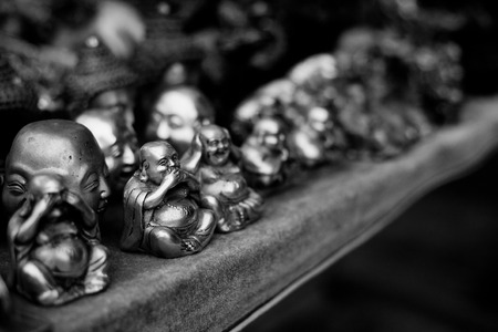 small buddah statues for sale on the shelf closeup black and white