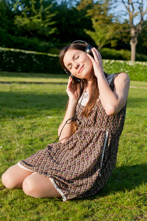 cute girl listening to music  sitting in the grass sunny summer day