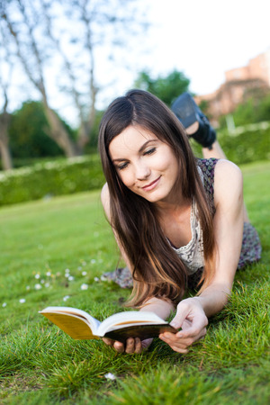 pretty girl reading a book lying on the grass summer day Stock Photo