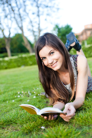 pretty smiling girl reading a book lying on the grass summer day