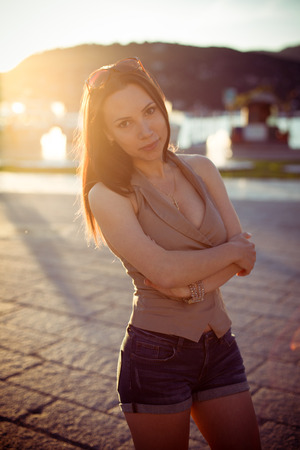Beautiful girl standing on the street during the sunset summer day