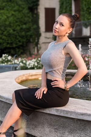 Stylish attractive model sitting by the fountain summer Stock Photo