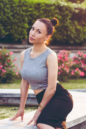 Stylish attractive model sitting by the fountain beautiful sunset Stock Photo