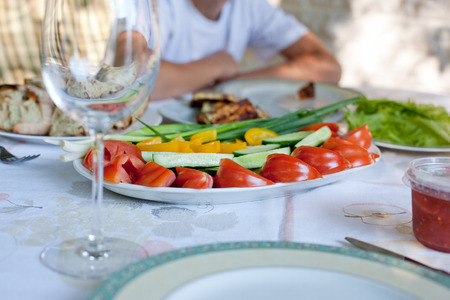 plate with vegetables on the table, dinner outdoors, summer day