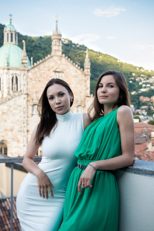 Two attractive stylish girl on summer terrace, beautiful city view Stock Photo