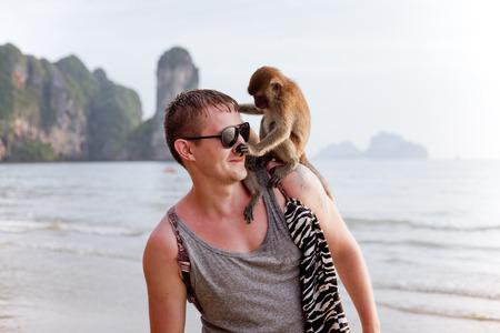 monos: Hombre joven con el mono divertido que se sienta en su hombro, tocando su nariz, país tropical