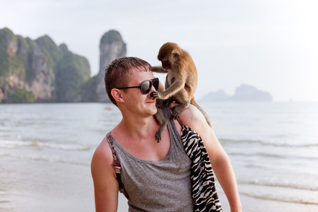 Young man with funny monkey sitting on his shoulder, touching his nose, tropical country