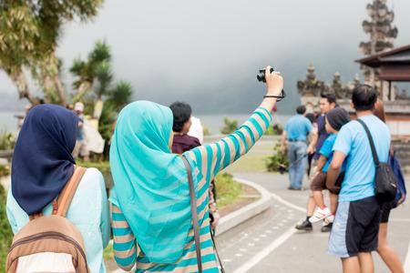person traveling: Dos mujeres musulmanas jóvenes que toman selfie, vista desde la parte de atrás