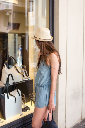 attractive stylish girl looking at display window, summer day
