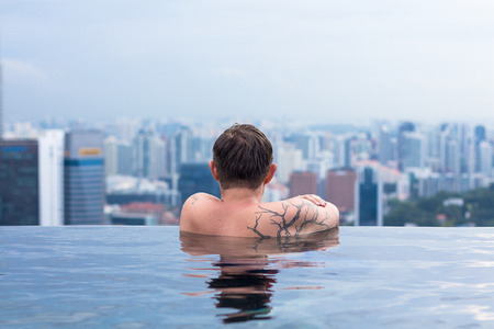 Young tattooed man enjoying the view from infinity pool, rear view