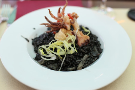 Black ink risotto with seafood in restaurant