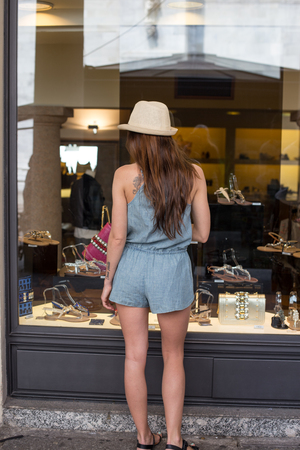 Stylish girl standing near display window on the street