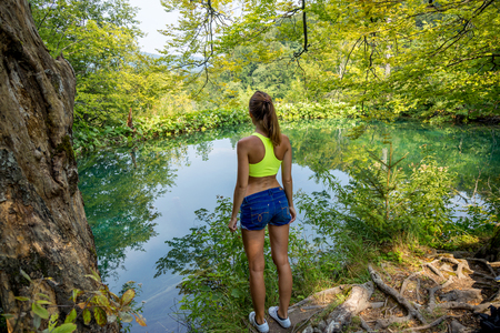 girl standing near the beautiful forest lake, enjoying the view, rear view