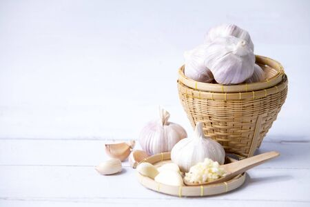 Fresh garlic, Garlic, Bulb Cloves in wooden spoon and basket on white wooden table.Place for text, copy space Concept of healthy food, ,selective focus.
