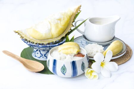 Sweet Sticky Rice With Durian And Coconut Milk Sauce,Thai sweet sticky rice with durian, Thai style tropical dessert, isolated on white background, selective focus.
