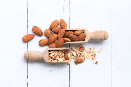Almonds crushed into pieces and almond in wooden spoon on a white background,Close up top view