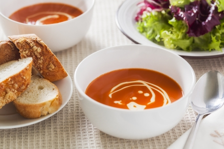 Tomato soup with swirled cream, side salad and crusty bread Stock Photo - 20261574