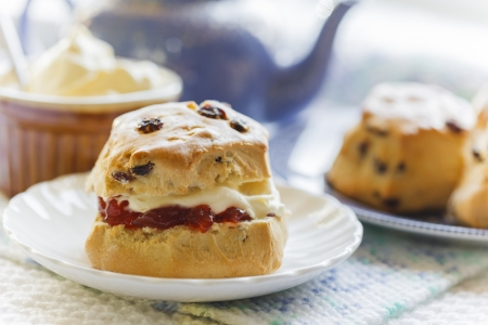 Traditional afternoon tea with scones, jam and cream, blue teapot and crockery, light and summery teashop menu Stock Photo