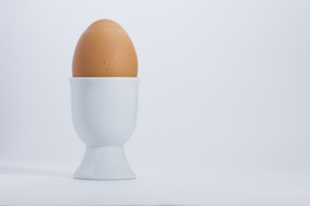 Isolated boiled egg in white egg cup for a nutritios and healthy breakfast thats good for you
