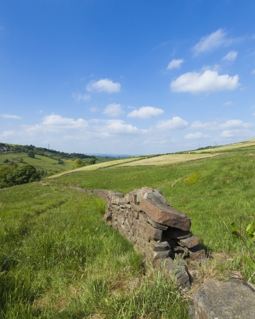 Yorkshire Landscape with fields and dry stone wall and lots of bright blue sky and clouds