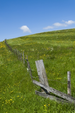 Broken wooden fence on grassy hillside with bright blue sunny skie