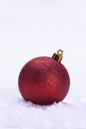 red glittery: Scintillante pallina di Natale rosso con oro topper sulla neve isolato su sfondo bianco Archivio Fotografico