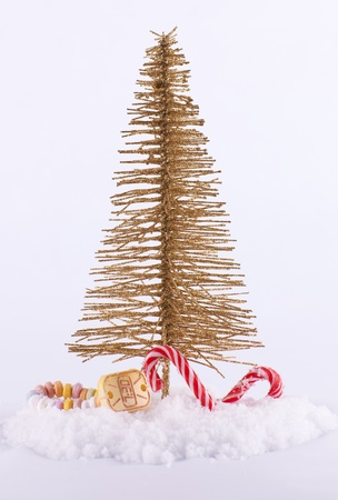 Novelty gold wire Christmas tree with candy and snow on white background