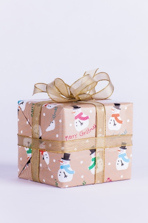 Wrapped Christmas present gift with bow and gold ribbon with snowmen on white background