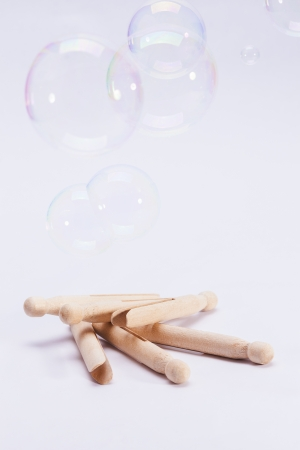 Wooden dolly pegs and bubbles on white background Stock Photo