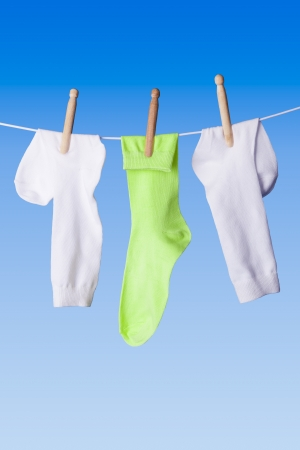 White and green socks with dolly pegs hanging out on washing line against blue background Stock Photo