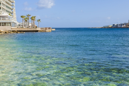 Crystal Clear waters with palm trees and blue sky at Spinola Bay on the island of Malta