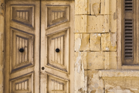 Old wooden doors and stone work on traditional built house in Malta