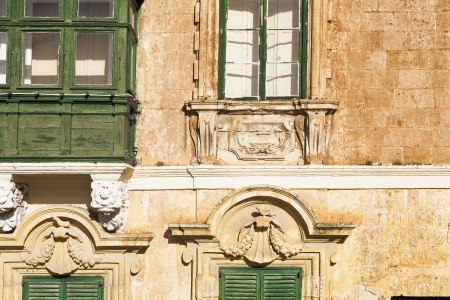 Old wooden doors windows and elaborate stone work on house on the island of Malta Stock Photo