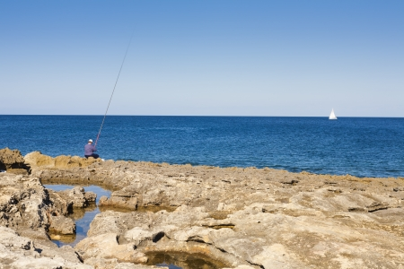 SIngle  fisherman nd  yacht on blue sea with rocky beach on the island of Malta Stock Photo