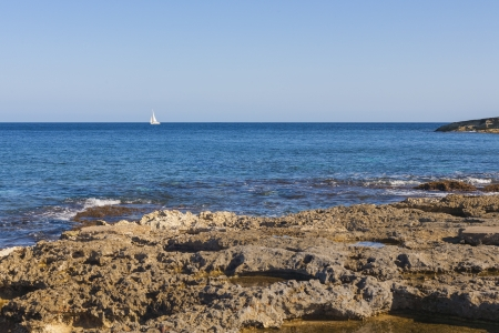 SIngle yacht on blue sea with rocky beach on the island of Malta