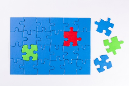 Jigsaw puzzle with different colored pieces signifying concepts of diversity, equality, community and being the odd one out