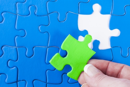 Close up of womans hand placing missing piece in Jigsaw puzzle  signifying problem solving and decision making Stock Photo