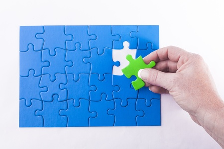 Womans hand placing green Jigsaw puzzle piece in blue puzzles signifying diversity and equality Stock Photo