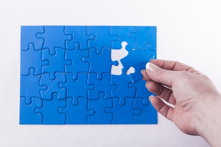 Womans hand placing missing piece in Jigsaw puzzle  signifying problem solving and decision making