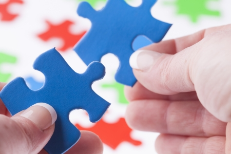 close fitting: Womans hands fitting jigsaw puzzle pieces together, close up with shallow depth of field