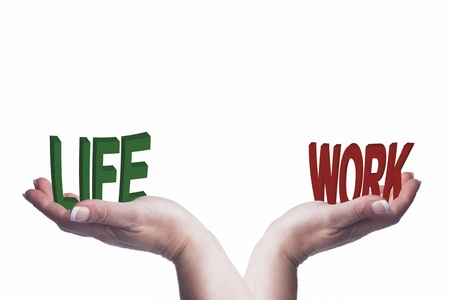 Conceptual image showing womans hands balancing life and work words to represent work-life balance concept