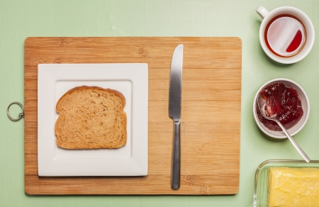 Sliced brown bread on square plate with herbal tea, jam, butter and knife on wooden chopping board