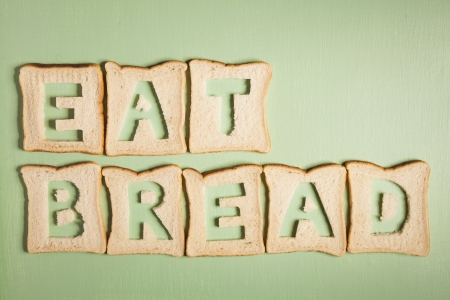 Eat bread text carved out of white bread slices on wooden background