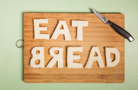 Eat bread text carved out of white bread slices on wooden chopping board with cooks knife Stock Photo