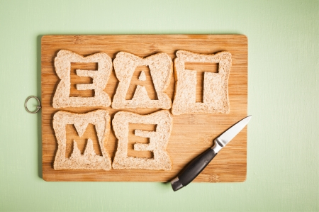 Eat me text carved out of brown bread slices on wooden chopping board with chefs kitchen knife, hunger, hungry Stock Photo